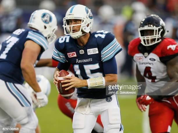 Ricky Ray of the Toronto Argonauts rolls Out to pass with Micah Johnson of the Calgary Stampeders in pursuit during a CFL game at BMO Field on August...