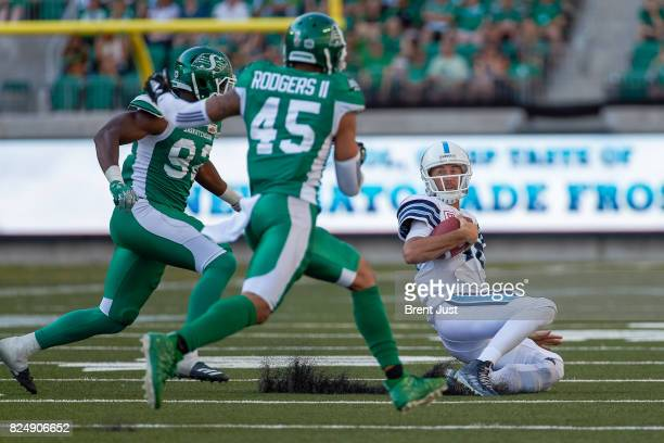 Ricky Ray of the Toronto Argonauts slides after scrambling to avoid a hit from Tobi Antigha and Kacy Rodgers II of the Saskatchewan Roughriders in...