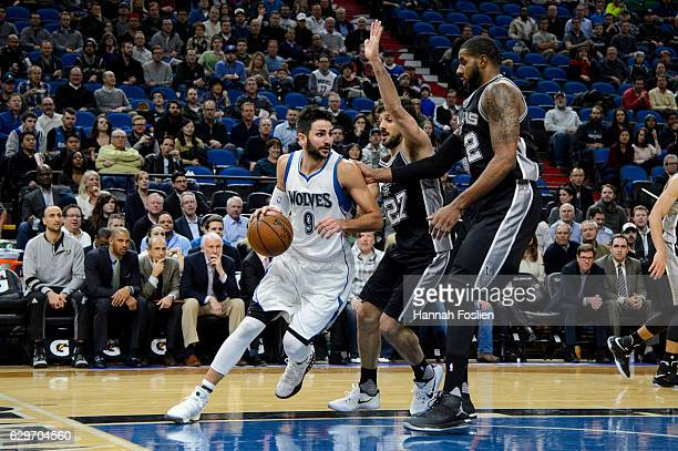 Ricky Rubio of the Minnesota Timberwolves dribbles the ball against Nicolas Laprovittola and LaMarcus Aldridge of the San Antonio Spurs during the...