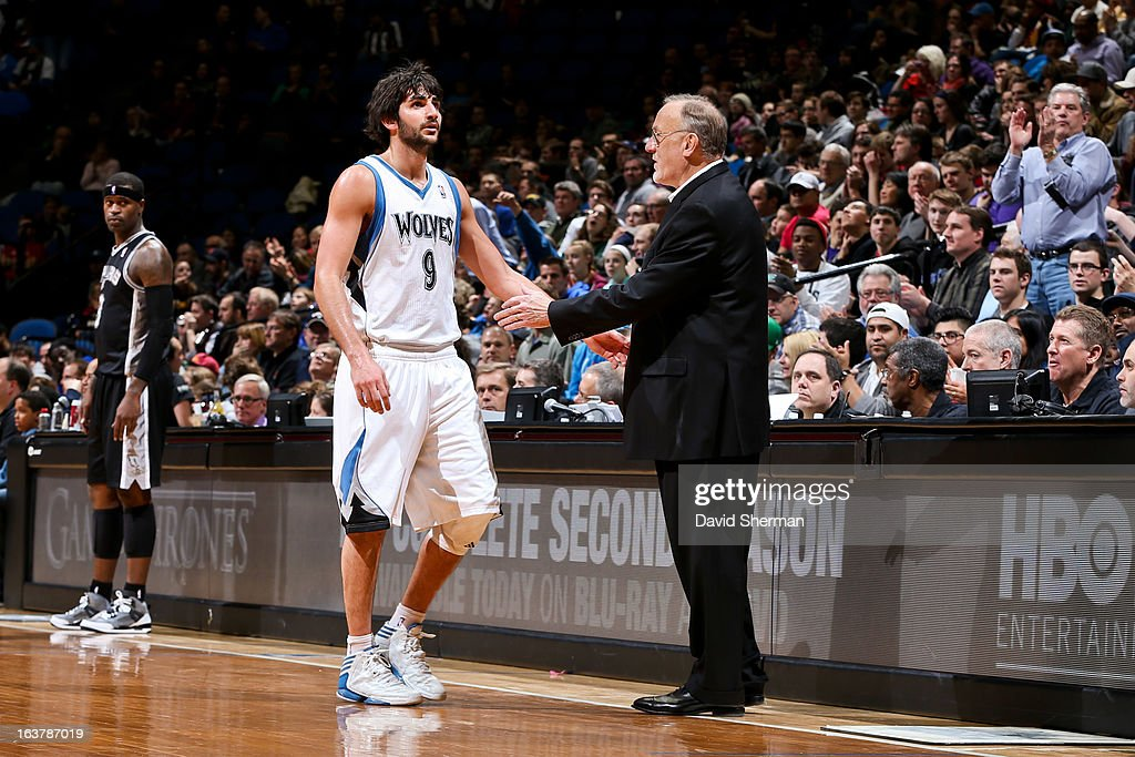Ricky Rubio #9 of the Minnesota Timberwolves greets head coach Rick Adelman on his way to the bench during a game against the San Antonio Spurs on March 12, 2013 at Target Center in Minneapolis, Minnesota.