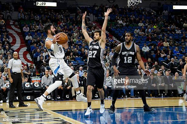 Ricky Rubio of the Minnesota Timberwolves passes the ball away from Nicolas Laprovittola and LaMarcus Aldridge of the San Antonio Spurs during the...