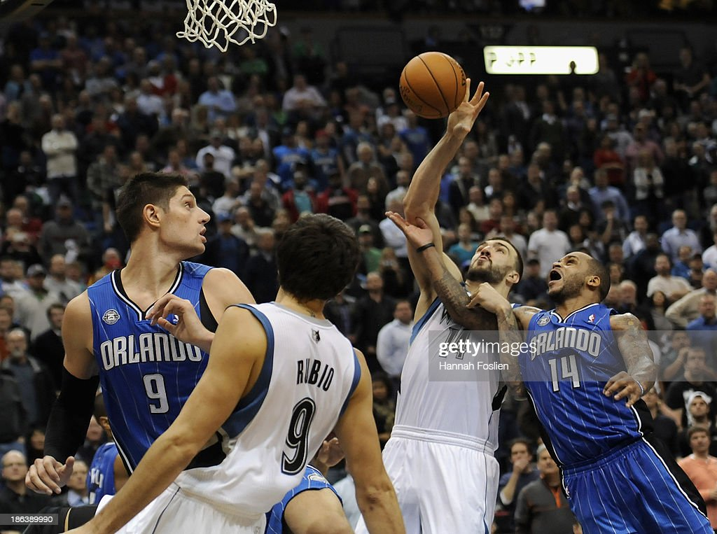 Ricky Rubio #9 of the Minnesota Timberwolves passes the ball to teammate Nikola Pekovic #14 while Nikola Vucevic #9 of the Orlando Magic defends Rubio and Jameer Nelson #14 of the Orlando Magic defends Pekovic during the fourth quarter of the season opening game on October 30, 2013 at Target Center in Minneapolis, Minnesota. The Timberwolves defeated the Magic 120-115 in overtime.