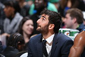 Ricky Rubio of the Minnesota Timberwolves watches the game from the bench against the Charlotte Hornets on March 22 2015 at Target Center in...