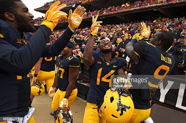 Ricky Rumph KJ Dillon and the teammates of the West Virginia Mountaineers celebrate after defeating the Maryland Terrapins during an NCAA college...