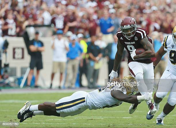 Ricky SealsJones of the Texas AM Aggies gives a stiff arm to Jayon Brown of the UCLA Bruins as he runs with the ball after a reception in the first...
