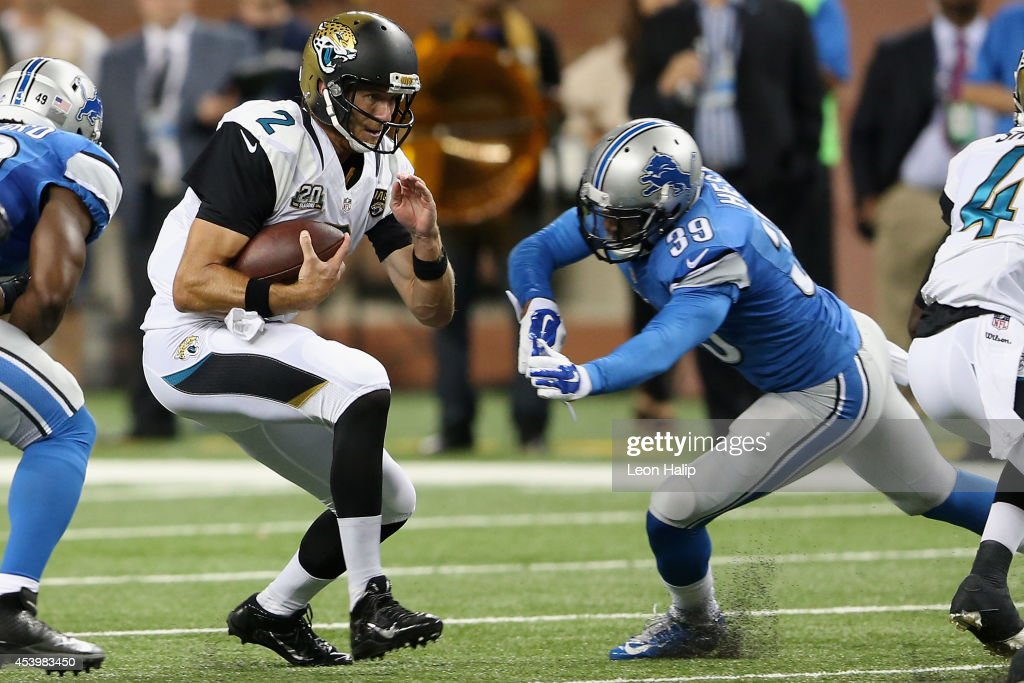 Ricky Stanzi #2 of the Jacksonville Jaguars tries to avoid the tackle by Aaron Hester #39 of the Detroit Lions in the fourth quarter during a preseason game at Ford Field on August 22, 2014 in Detroit, Michigan.
