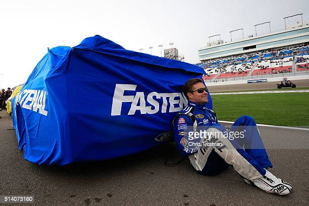 Ricky Stenhouse Jr driver of the Fastenal Ford Fusion Ford sits next to his covered car prior to the start of the NASCAR Sprint Cup Series Koblat 400...