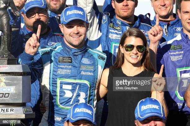 Ricky Stenhouse Jr driver of the Fifth Third Bank Ford poses with his girlfriend Danica Patrick driver of the Aspen Dental Ford in Victory Lane after...