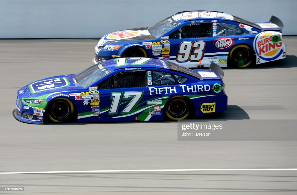 Ricky Stenhouse Jr., driver of the #17 Fifth Third Ford, races Travis Kvapil, driver of the #93 Burger King / Dr. Pepper Toyota, during the NASCAR Sprint Cup Series 44th Annual Pure Michigan 400 at Michigan International Speedway on August 18, 2013 in Brooklyn, Michigan.