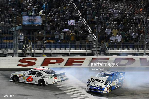 Ricky Stenhouse Jr driver of the RickyvsTrevorcom Ford crosses the finish line to win ahead of Carl Edwards driver of the Fastenal Ford after...