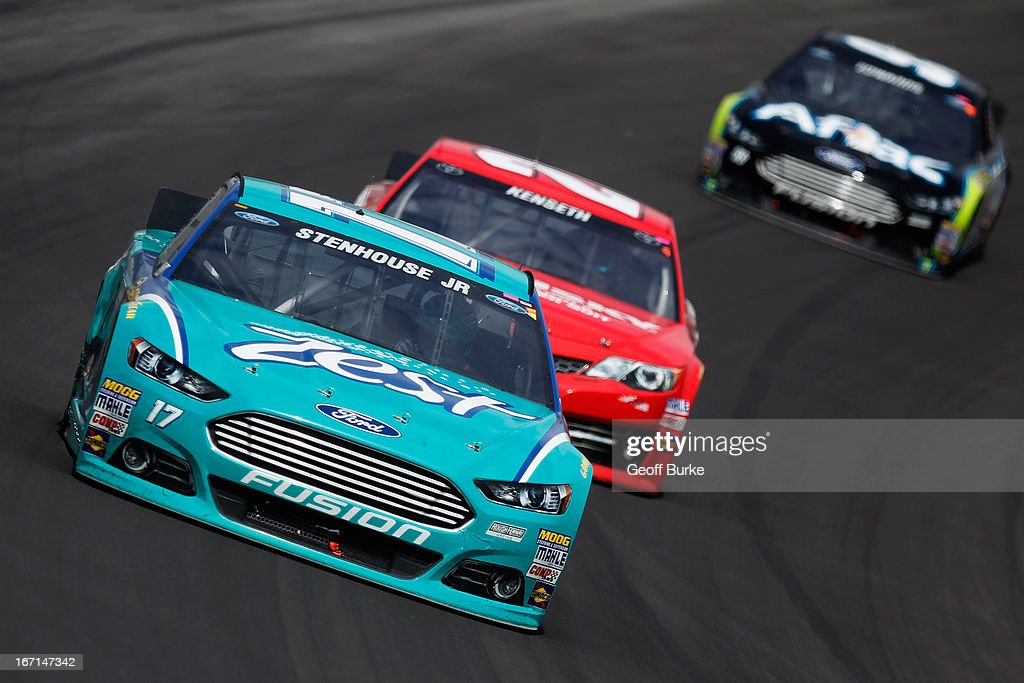 Ricky Stenhouse Jr., driver of the #17 Zest Ford, leads Matt Kenseth, driver of the #20 The Home Depot/Husky Toyota, and Carl Edwards, driver of the #99 Aflac Ford, during the NASCAR Sprint Cup Series STP 400 at Kansas Speedway on April 21, 2013 in Kansas City, Kansas.