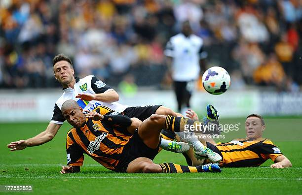 Ricky Van Wolfswinkel of Norwich City battles with James Chester and Curtis Davies of Hull City during the Barclays Premier League match between Hull...