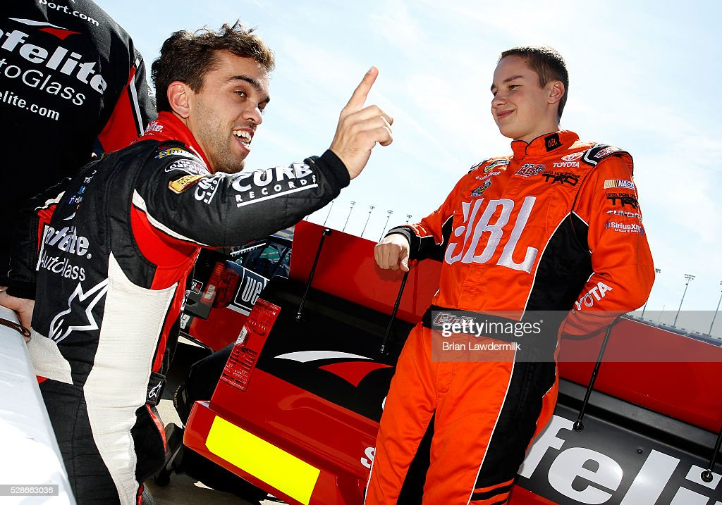 Rico Abreu, driver of the #98 Safelite Toyota, speaks with Christopher Bell, driver of the #4 JBL Toyota, during qualifying for the NASCAR Camping World Truck Series Toyota Tundra 250 at Kansas Speedway on May 6, 2016 in Kansas City, Kansas.