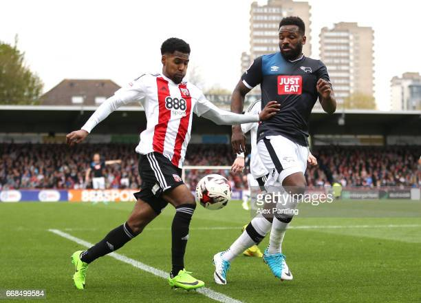 Rico Henry of Brentford and Darren Bent of Derby County in action during the Sky Bet Championship match between Brentford and Derby County at Griffin...