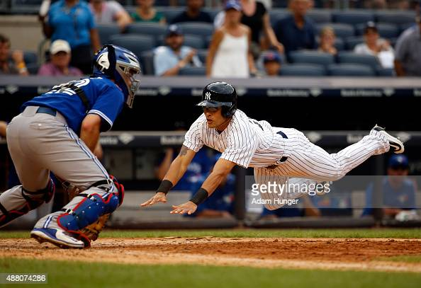 Rico Noel of the New York Yankees scores in the eighth inning past Josh Thole of the Toronto Blue Jays at Yankee Stadium on September 13 2015 in the...