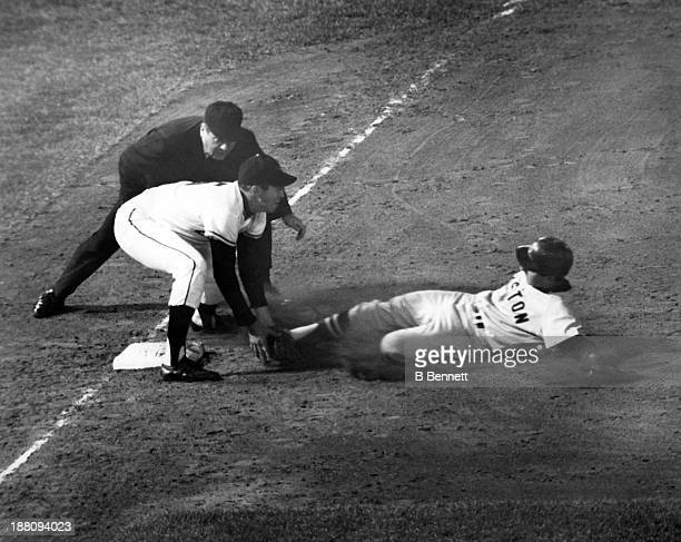 Rico Petrocelli of the Boston Red Sox is tagged out by third baseman Brooks Robinson of the Baltimore Orioles as umpire John Rice waits to make the...