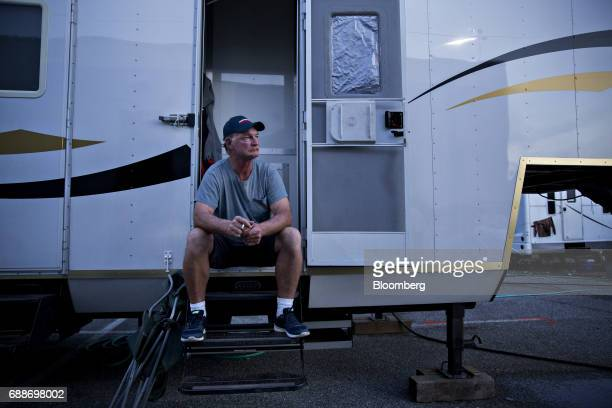 A ride operator and foreman smokes a cigarette outside his sleeping trailer during the Dreamland Amusements carnival in the parking lot of the Marley...