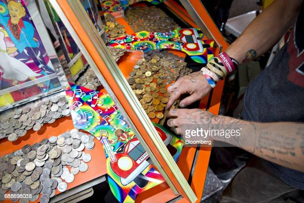 A ride operator arranges coins in a game before his shift during the Dreamland Amusements carnival in the parking lot of the Marley Station Mall in...