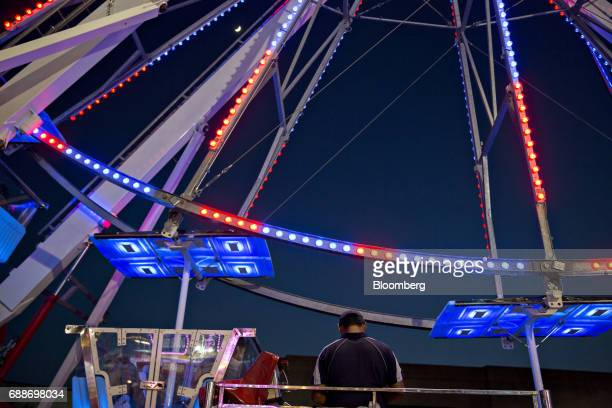 A ride operator stands at the Dream Wheel during the Dreamland Amusements carnival in the parking lot of the Marley Station Mall in Glen Burnie...
