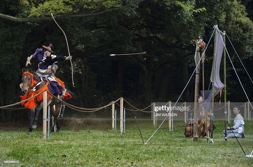 A rider fires an arrow during a horseback archery demonstration for US President Obama at the Meiji Shrine in Tokyo on April 24, 2014. Obama earlier vowed to defend Japan if China attacks over a tense territorial dispute, but also urged Beijing to help stop North Korea from forging ahead with its 'dangerous' nuclear programme. AFP PHOTO / Jim WATSON
