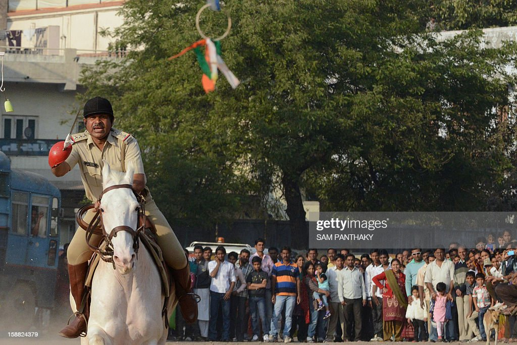 A rider from the elite Gujarat Mounted Police Force prepares to lance a target during an equestrian display in Ahmedabad on December 30, 2012. The event was organised as part of the ongoing Kankariya Carnival. AFP PHOTO / Sam PANTHAKY