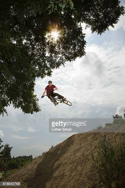 A BMX rider in mid-air at the top of a mud slope