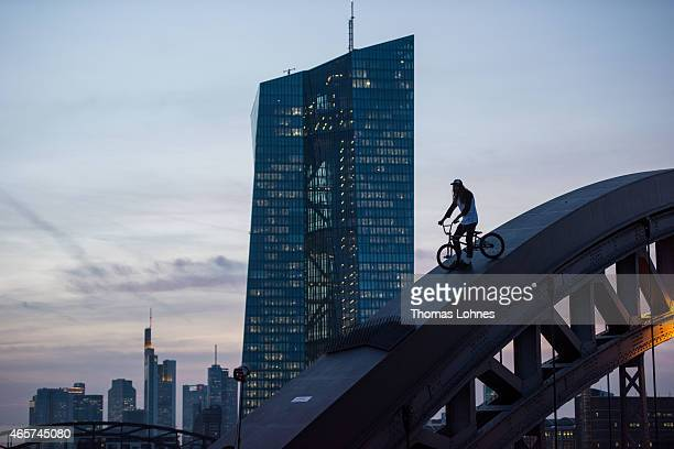 BMX rider jumps over a nail plate at a 'Osthafen' bridge arch with the the new headquaters of the European Central Bank and the skyline of Frankfurt...