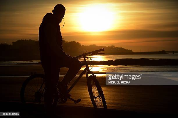 A rider looks at the sunset in Vigo northwestern Spain on December 30 2014 AFP PHOTO / MIGUEL RIOPA