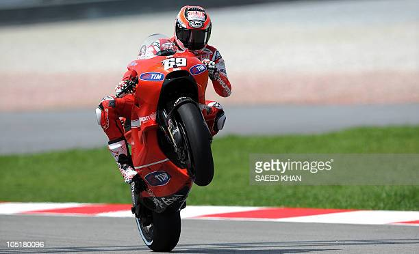 US rider Nicky Hayden of Ducati does a wheelie to celebrate second pole position at the end of the qualifying round of the Malaysian Grand Prix...