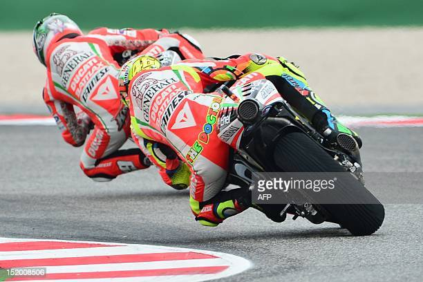 US rider Nicky Hayden rides ahead of Italian rider Valentino Rossi of the Ducati team during the third free practice of the MotoGP San Marino Grand...