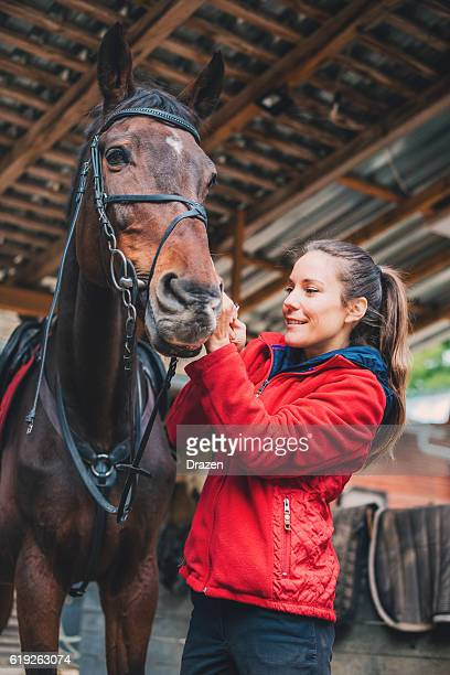 Rider putting reins on her mare before training