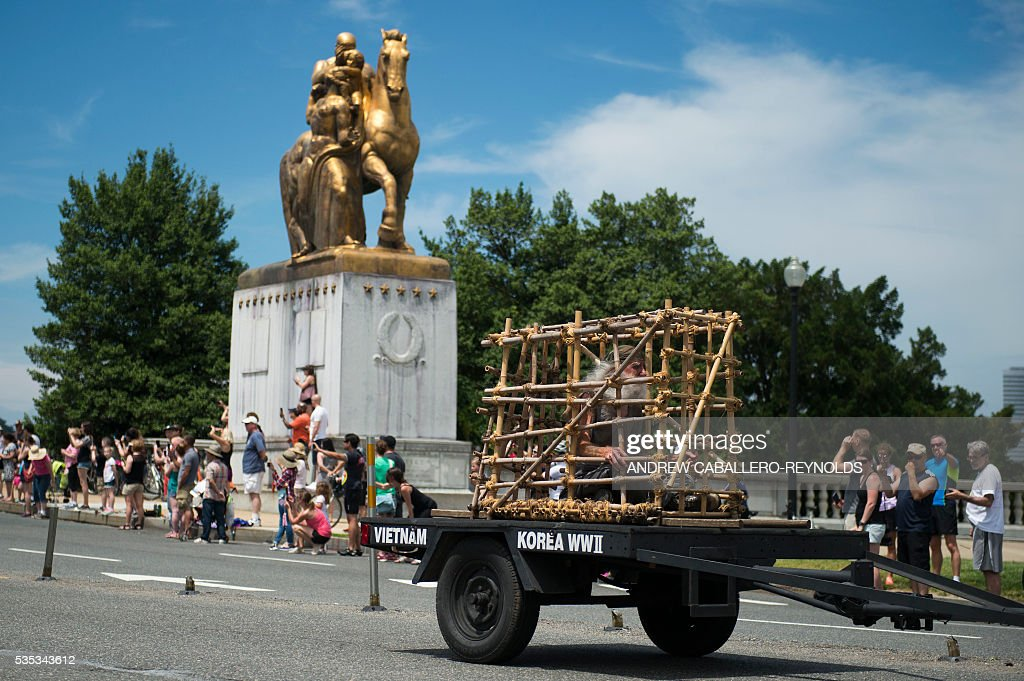 A rider representing a prisoner of war, rides in a cage during the Rolling Thunder rally in Washington, DC on May 29, 2016. Rolling Thunder is an advocacy group dedicated to raising awareness for American Prisoners of War and warriors currently missing in action. / AFP / andrew caballero-reynolds