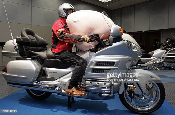 A rider shows off the world's first production motorcyle airbag system at Honda's headquarters in Tokyo 08 September 2005 Honda put the new airbag...