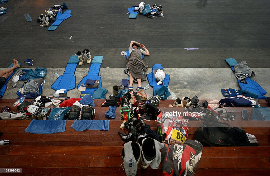 A rider sleeps in Cachi after the Stage 7 of the Dakar Rally 2013 between Calama and Salta, Argentina, on January 11, 2013. The rally takes place in Peru, Argentina and Chile January 5-20. AFP PHOTO / FRANCK FIFE
