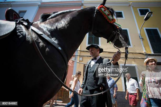 A rider waits past his horse during the traditional San Juan festival in the town of Ciutadella on the Balearic Island of Menorca on the eve of Saint...