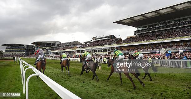 Riders and horses compete in the first race of the day The Gaskells Waste Management Handcap Hurdle on the final day of the Grand National Festival...