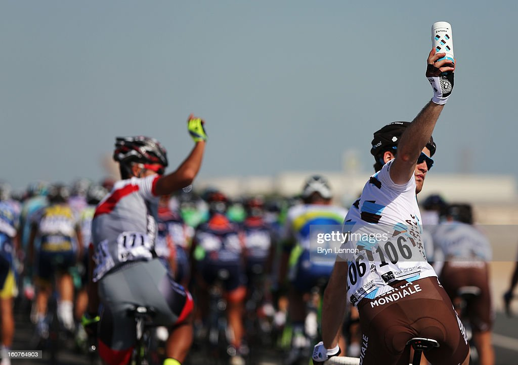 Riders at the back of the peloton signal to their team cars for more water bottles during stage three of the Tour of Qatar from Alwakra to Mesaieed on February 5, 2013 in Doha, Qatar.