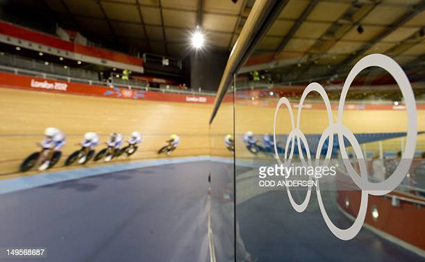 Riders from the South Korean team pass by an Olympic logo as they power past during a training session in the velodrome at The Olympic Park in London...