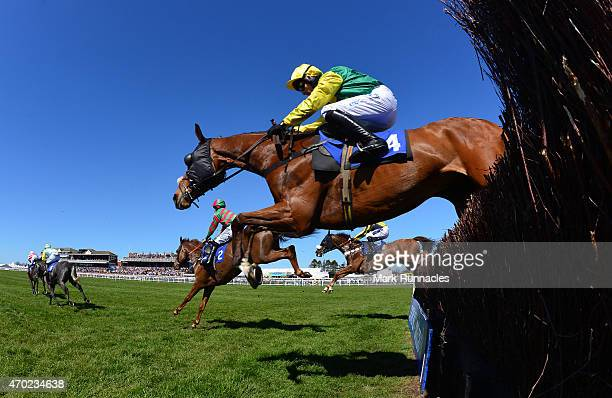Riders jump the first fence during The Weatherbys Private Banking Novices Limited Handicap Steeple Chase on the second day of the Scottish Grand...