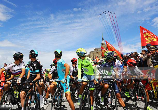 Riders look on as jets fly overhead prior to Stage One of Le Tour de France 2016 on July 2 2016 in Le MontSaintMichel France Le MontSaintMichel hosts...