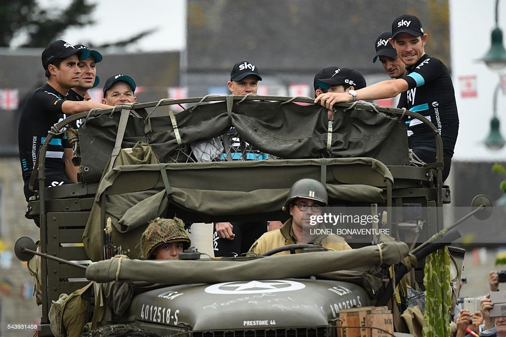 Riders of Great Britain's Sky cycling team take part in a parade aboard an World War II US army vehicle during the team presentation ceremony in Sainte-Mere-Eglise, Normandy, on July 30, 2016, two days before the start of the 103rd edition of the Tour de France cycling race. The 2016 Tour de France will start on July 2 in the streets of Le Mont-Saint-Michel and ends on July 24, 2016 down the Champs-Elysees in Paris. / AFP / LIONEL