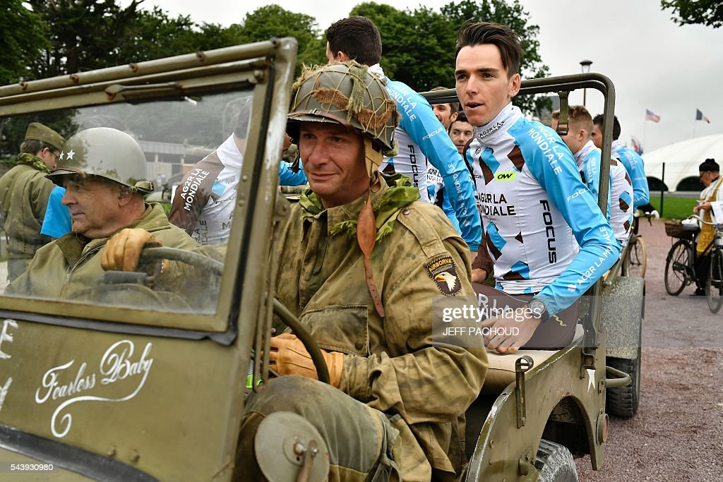 Riders of France's AG2R La Mondiale cycling team, including France's Romain Bardet (R), take part in a parade aboard an World War II US army vehicle during the team presentation ceremony in Sainte-Mere-Eglise, Normandy, on July 30, 2016, two days before the start of the 103rd edition of the Tour de France cycling race. The 2016 Tour de France will start on July 2 in the streets of Le Mont-Saint-Michel and ends on July 24, 2016 down the Champs-Elysees in Paris. / AFP / jeff pachoud