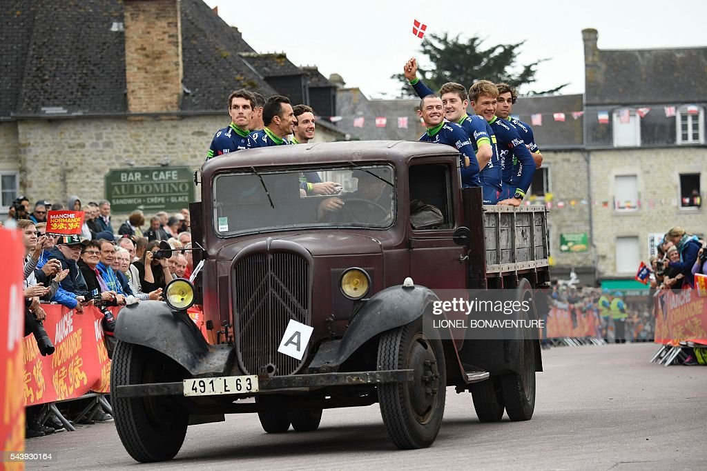 Riders of the Australia's Orica Greenedge cycling team take part in a parade aboard an World War II US army vehicle during the team presentation ceremony in Sainte-Mere-Eglise, Normandy, on July 30, 2016, two days before the start of the 103rd edition of the Tour de France cycling race. The 2016 Tour de France will start on July 2 in the streets of Le Mont-Saint-Michel and ends on July 24, 2016 down the Champs-Elysees in Paris. / AFP / LIONEL