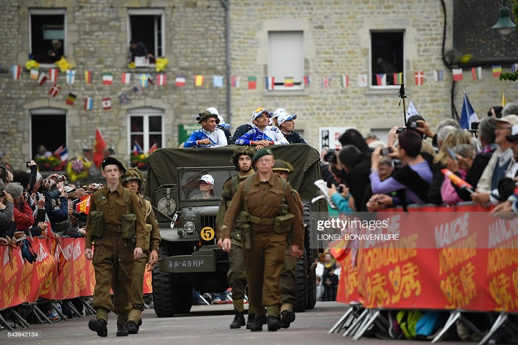 Riders of the France's FDJ cycling team take part in a parade aboard an World War II US army vehicle, behind men dressed as 1940s soldiers, during the parade of the team presentation ceremony in Sainte-Mere-Eglise, Normandy, on June 30, 2016, two days before the start of the 103rd edition of the Tour de France cycling race. The 2016 Tour de France will start on July 2 in the streets of Le Mont-Saint-Michel and ends on July 24, 2016 down the Champs-Elysees in Paris. / AFP / LIONEL