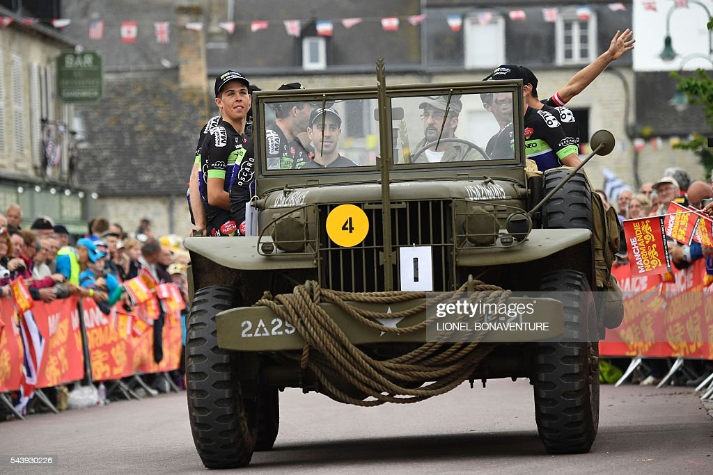 Riders of the France's Fortuneo - Vital Concept cycling team take part in a parade aboard an World War II US army vehicle during the team presentation ceremony in Sainte-Mere-Eglise, Normandy, on July 30, 2016, two days before the start of the 103rd edition of the Tour de France cycling race. The 2016 Tour de France will start on July 2 in the streets of Le Mont-Saint-Michel and ends on July 24, 2016 down the Champs-Elysees in Paris. / AFP / LIONEL