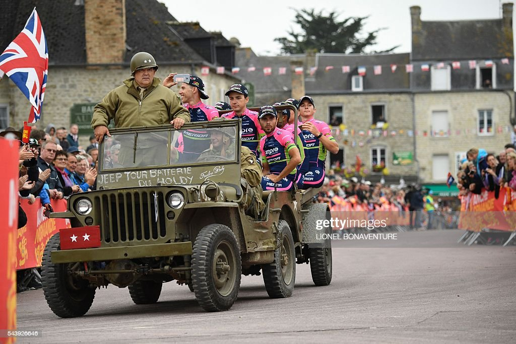 Riders of the Italy's Lampre-Merida cycling team take part in a parade aboard an World War II US army vehicle during the team presentation ceremony in Sainte-Mere-Eglise, Normandy, on July 30, 2016, two days before the start of the 103rd edition of the Tour de France cycling race. The 2016 Tour de France will start on July 2 in the streets of Le Mont-Saint-Michel and ends on July 24, 2016 down the Champs-Elysees in Paris. / AFP / LIONEL