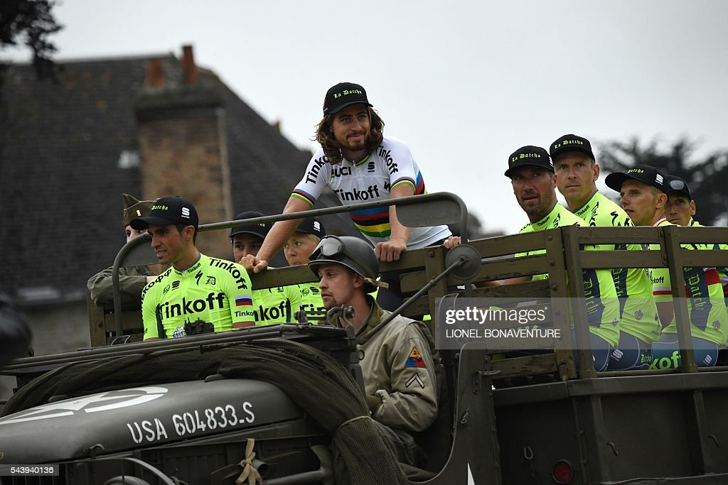 Riders of the Russia's Tinkoff cycling team, including Spain's Alberto Contador (L) and Slovakia's Peter Sagan (C), take part in a parade aboard an World War II US army vehicle during the team presentation ceremony in Sainte-Mere-Eglise, Normandy, on June 30, 2016, two days before the start of the 103rd edition of the Tour de France cycling race. The 2016 Tour de France will start on July 2 in the streets of Le Mont-Saint-Michel and ends on July 24, 2016 down the Champs-Elysees in Paris. / AFP / LIONEL
