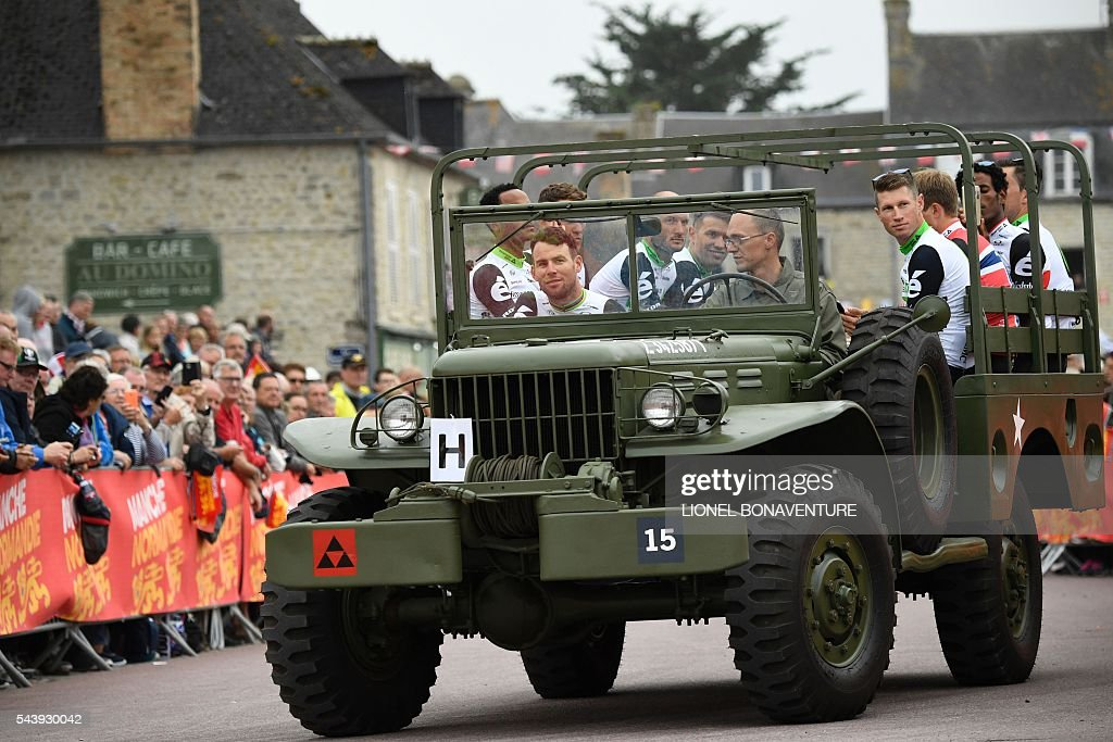 Riders of the South Africa's Dimension Data cycling team, including Great Britain's Mark Cavendish (L) take part in a parade aboard an World War II US army vehicle during the team presentation ceremony in Sainte-Mere-Eglise, Normandy, on July 30, 2016, two days before the start of the 103rd edition of the Tour de France cycling race. The 2016 Tour de France will start on July 2 in the streets of Le Mont-Saint-Michel and ends on July 24, 2016 down the Champs-Elysees in Paris. / AFP / LIONEL