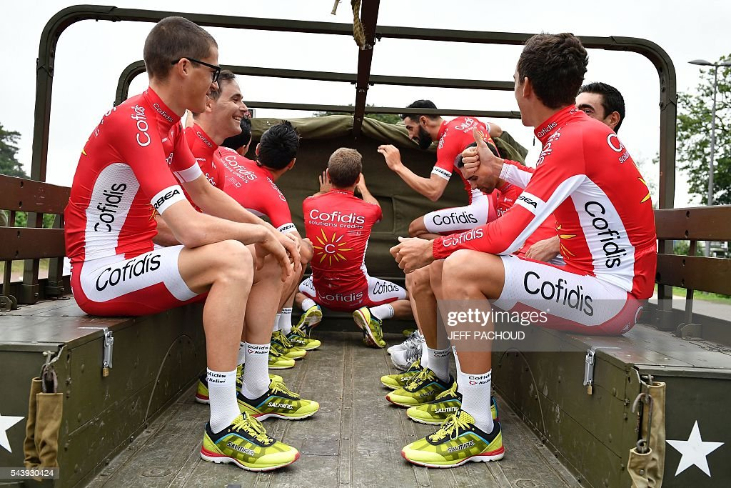 Riders of the France's Cofidis cycling team take part in a parade aboard an World War II US army vehicle during the team presentation ceremony in Sainte-Mere-Eglise, Normandy, on July 30, 2016, two days before the start of the 103rd edition of the Tour de France cycling race. The 2016 Tour de France will start on July 2 in the streets of Le Mont-Saint-Michel and ends on July 24, 2016 down the Champs-Elysees in Paris. / AFP / jeff pachoud