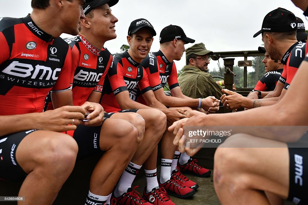 Riders of the USA's BMC Racing cycling team, including Australia's Richie Porte (3rdL), take part in a parade aboard an World War II US army vehicle during the team presentation ceremony in Sainte-Mere-Eglise, Normandy, on July 30, 2016, two days before the start of the 103rd edition of the Tour de France cycling race. The 2016 Tour de France will start on July 2 in the streets of Le Mont-Saint-Michel and ends on July 24, 2016 down the Champs-Elysees in Paris. / AFP / jeff pachoud